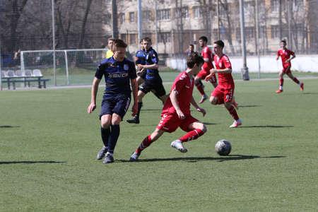 Odessa, Ukraine - April 11, 2021: Local children's football teams U-17 play on artificial grass of stadium. Football on field with artificial grass for soccer games. Children are playing football