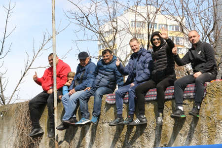Odessa, Ukraine - April 7, 2021: Parents of children's soccer team players age of 14 during OVID19 pandemic and ban on spectators illegally watch game of children of football players sitting on fence