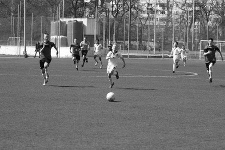 Odessa, Ukraine - April 7, 2021: Local children's football teams U-14 play on artificial grass of stadium. Football on field with artificial grass for soccer games. Children are playing football