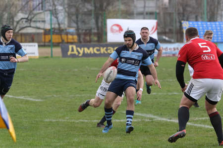 ODESSA, UKRAINE - April 17, 2021: Rugby Cup 7. Odessa Polytechnic Derby - blue, CREDO - red. Tense moment of men's rugby match. Dramatic and challenging men's rugby derby. Men fight on rugby field Redakční