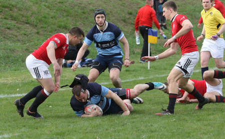 ODESSA, UKRAINE - April 17, 2021: Rugby Cup 7. Odessa Polytechnic Derby - blue, CREDO - red. Tense moment of men's rugby match. Dramatic and challenging men's rugby derby. Men fight on rugby field