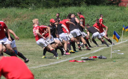 Odessa, Ukraine - June 23, 2021: Odessa National Team CREDO (red) - OLYMP-Kharkiv (yellow) in rugby 7s. Sharp aggressive fight of male rugby players for ball. Dynamic play on green grass of stadium