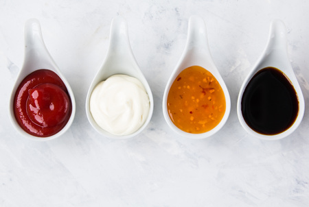 Four white cups with sauces: ketchup, mayonnaise, soy sauce stand against a dark background Stock Photo