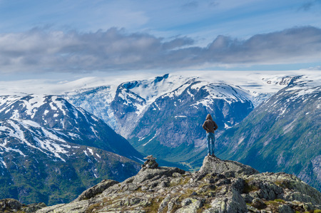 Men on the edge of Myrhyrna mountain viewing Jostedalsbreen and Nigardsbreen glaciers, Norway photo
