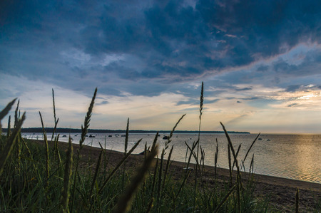 Dramatic cloudscape sunset at sea gulf with tall grass on beach Stock Photo