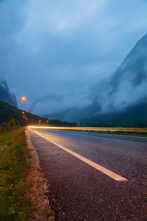 Wet asphalt road in mountain fog with long exposure car light photo