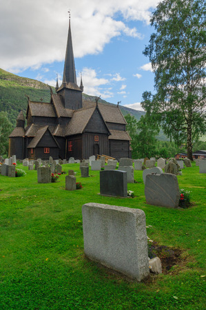 stave: Wooden building of antique norwegian stave chapel and cemetery in Lom Stock Photo