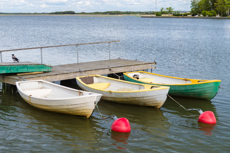 rowboats: Three rowboats at wooden dock with buoy waiting for customers