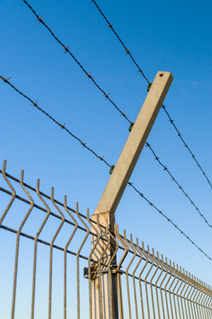 barbed wire fence: Security barbed wire fence against blue sky Stock Photo