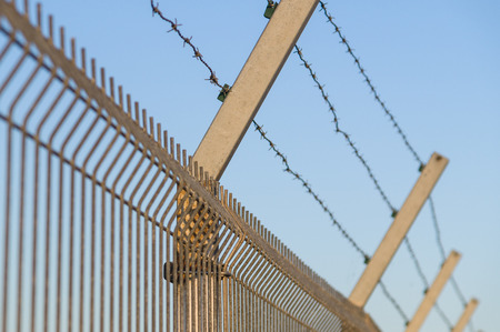 invade: Security post with barbed wire fence closeup