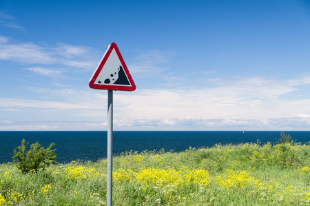 green sign: Precipice edge warning sign. Danger sea cliff hidden by grass and flowers