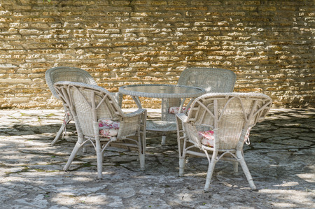 cane chair: Outdoor terrace at courtyard with limestone wall, cane chair furniture