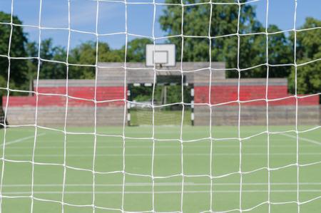 pasto sintetico: Fondo borroso de juegos al aire libre a través de red de la portería de fútbol Foto de archivo