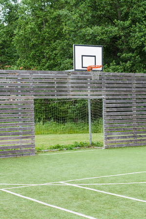 pasto sintetico: Meta del fútbol y aro de baloncesto en el patio al aire libre con el campo sintético
