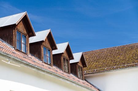 mansard: Tile roof and windows of mansard rooms against blue sky Stock Photo