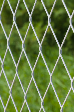 mesh fence: Defocused solid metallic mesh fence against green background