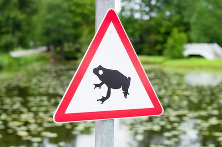 anuran: Traffic sign attends for frog migration, pond on background