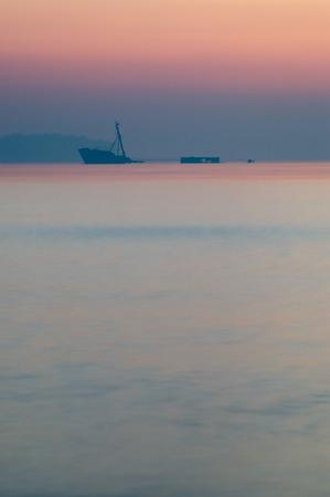 sunken: Partially sunken ship in after sunset haze