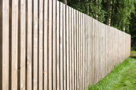 Typical wooden fence with green lawn and trees Foto de archivo
