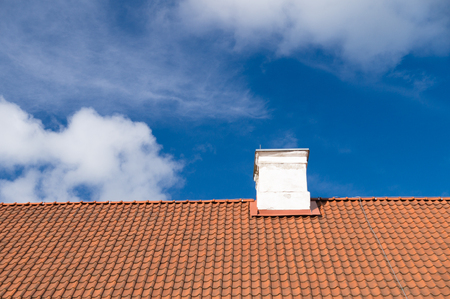 rooftile: Typical tiled roof and white chimney against blue sky Stock Photo