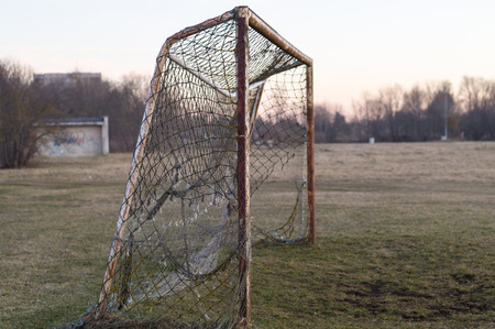 Old rusty soccer goal on sunset, nostalgia concept