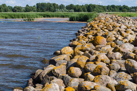 backwater: Ainazi North pier stones covered by yellow moss and backwater view, Latvia