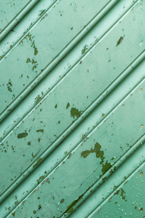 lopsided: Old green wooden wall with peeling paint and drops of water, diagonal pattern