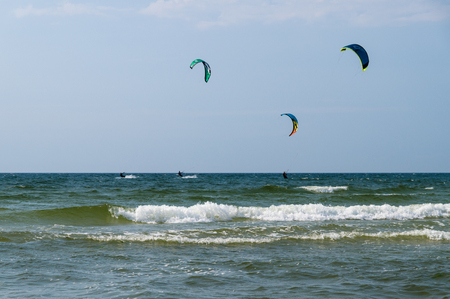 kiter: Silhouettes of three kiters ride on the waves of sea