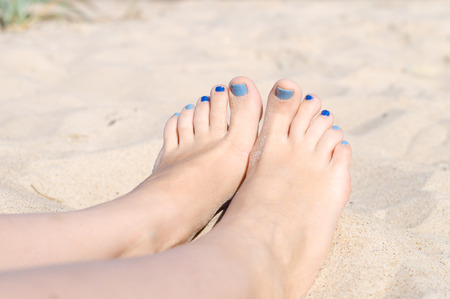 sandy feet: Woman sandy feet with blue nails pedicure relaxing on the beach