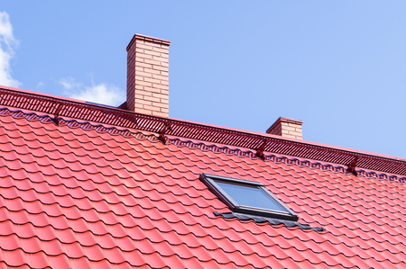 mansard: Brick chimney on red roof with mansard window
