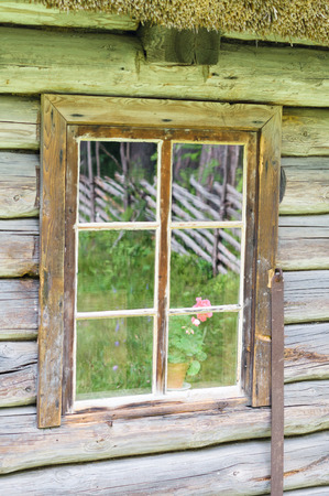 Window in old wooden rural house, courtyard reflection on glass