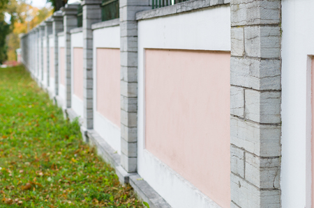 diminishing perspective: Pink and white concrete fence with stone columns, diminishing perspective