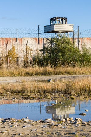 prison wall: Abandoned watch-tower and prison wall with reflection in puddle Stock Photo