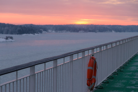 the north sea: Deck of ferry with life-buoy, winter sunrise on background