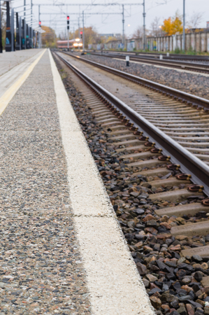 diminishing perspective: Railroad track, platform and train. Defocused image with diminishing perspective Stock Photo