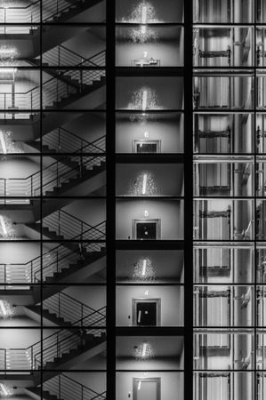stairwell: Abstract exterior of modern building. Staircase, lift and stairwell through transparent glass. Black and white concept