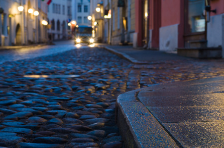 Early morning old town street with car glowing headlights. Blurred image with focus on foreground sidewalk