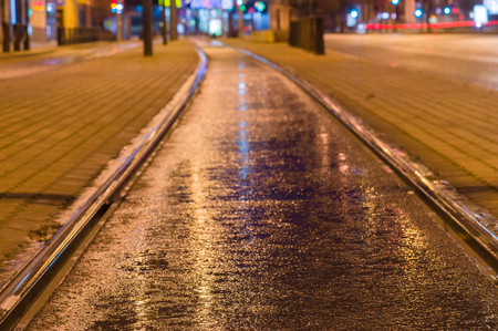 rail track: Tram rail track wet and shiny by night lights, blurred city background