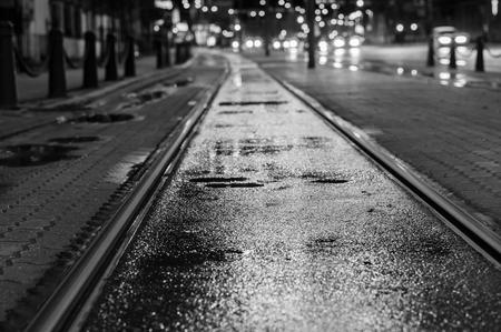 Nacht uitzicht op natte tramrails na regen. Vage verkeerslichten op de achtergrond, zwart en wit toon