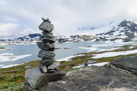 on lake: Balanced stack of stones against blurred background of higland lake and snowy mountains Stock Photo