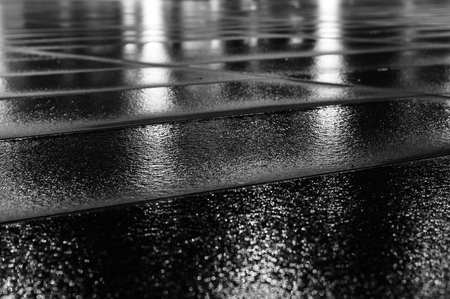 black block: Night light reflection on wet paving slab after rain. Black and white image with selective focus