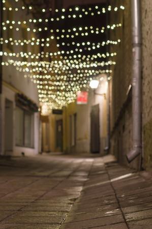 festoon: Blurred image of narrow city street decorated with illuminated festoon Stock Photo