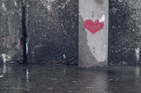 broken wall: Red heart symbol painted on a wet grunge wall Stock Photo