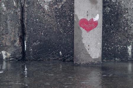 pared rota: símbolo de corazón rojo pintado en una pared del grunge mojado