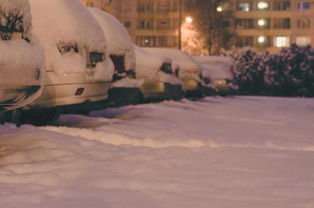 snowbound: Snowbound cars at urban parking, blurred view by night