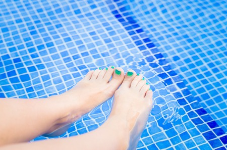 painted toes: Woman feet with green-blue pedicure relaxing in swimming pool water