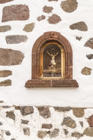 cross recess: Sculpture of Jesus Christ crucifixion in a niche of the wall, vertical view