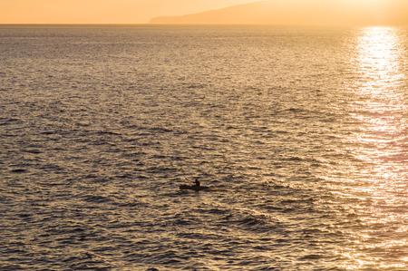 oar: Silhouette of kayak oar in sunset light, sun sparkles on water