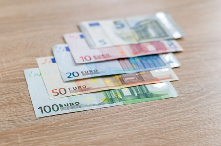5 to 10: Set of money banknotes: 5, 10, 20, 50 and 100 euro on wooden background, selective focus