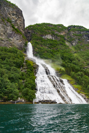 roaring sea: Waterfall called The Suitor flowing into Geirangerfjord, Norway Stock Photo